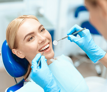 Happy young woman getting her teeth examined